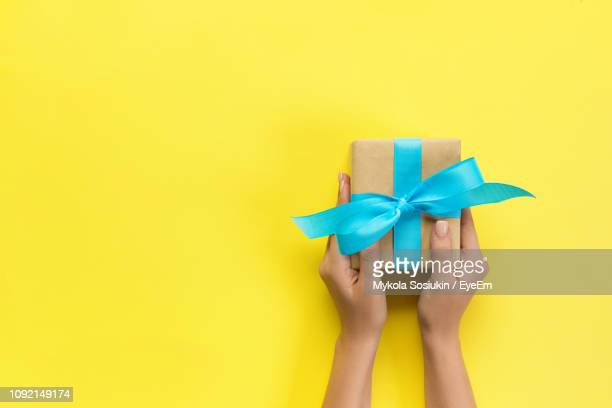 cropped hands of woman holding gift box on yellow background - gift hand stock-fotos und bilder
