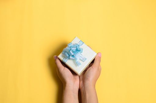 Cropped Hands Of Woman Holding Gift Box Over Yellow Background - gettyimageskorea