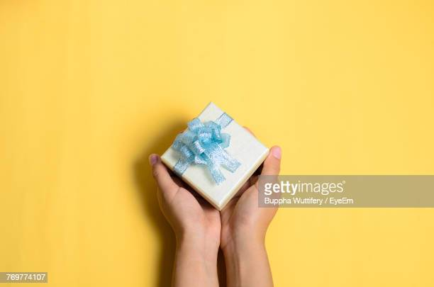 Cropped Hands Of Woman Holding Gift Box Over Yellow Background