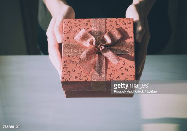 Cropped Hands Of Woman Holding Gift Over Table At Home