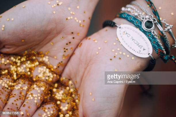 cropped hands of woman holding golden star shape glitters - ブレスレット ストックフォトと画像