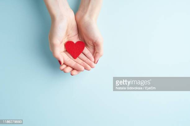 cropped hands of woman holding heart shape over blue background - heart shape stock pictures, royalty-free photos & images