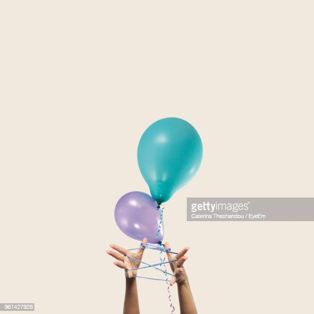 cropped hands of woman holding helium balloons against beige background - arto umano foto e immagini stock