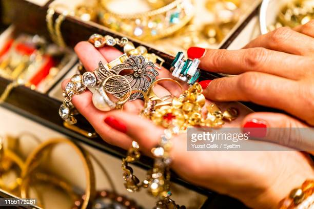 cropped hands of woman holding jewelries - jewellery stock pictures, royalty-free photos & images