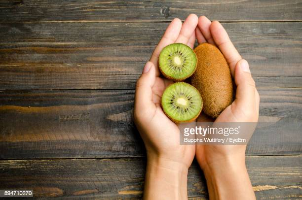 cropped hands of woman holding kiwi on table - kiwi fruit stock pictures, royalty-free photos & images