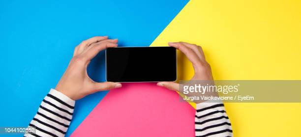 cropped hands of woman holding mobile phone over colored background - ツートンカラー ストックフォトと画像