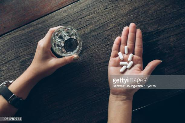 cropped hands of woman holding pills and drinking water in glass - dosis stock-fotos und bilder