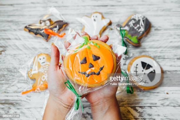 cropped hands of woman holding various cookies wrapped in plastic over wooden table during halloween - indulgence stock pictures, royalty-free photos & images