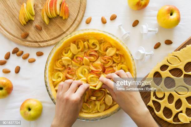 cropped hands of woman making apple pie - apple pie stock photos and pictures