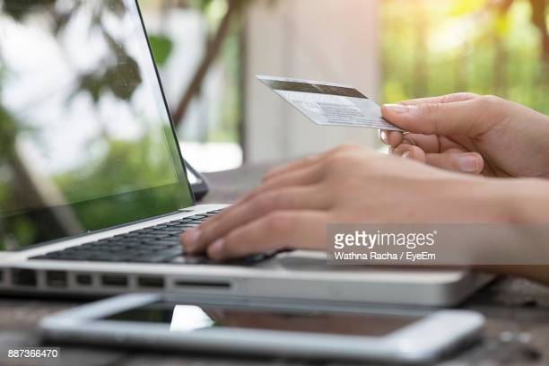cropped hands of woman making card payment while using laptop at table - 部分 ストックフォトと画像