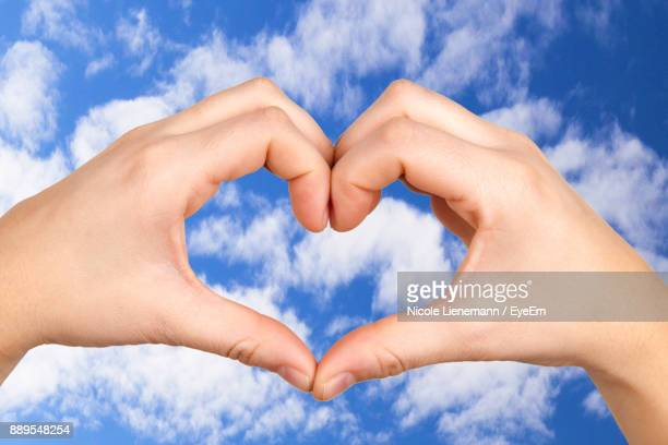 Cropped Hands Of Woman Making Heart Shape Against Blue Sky