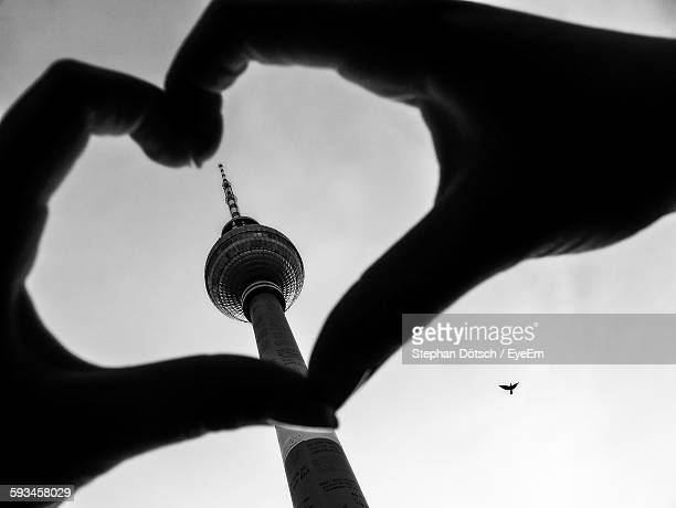 Cropped Hands Of Woman Making Heart Shape Against Fernsehturm
