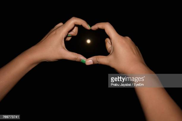 Cropped Hands Of Woman Making Heart Shape Against Moon