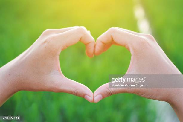 Cropped Hands Of Woman Making Heart Shape