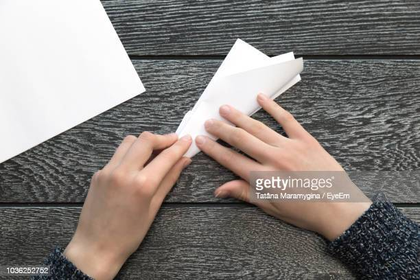 cropped hands of woman making paper airplane on wooden table - origami stock pictures, royalty-free photos & images