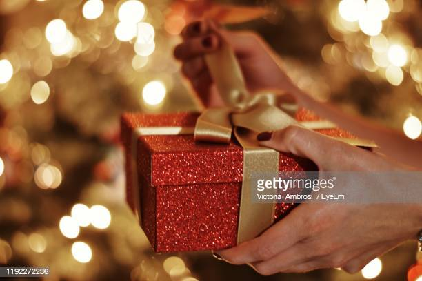 cropped hands of woman opening gift box against christmas lights - gifts stock pictures, royalty-free photos & images