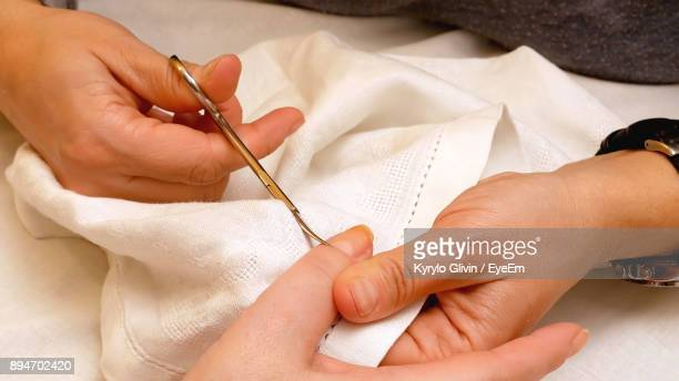 Cropped Hands Of Woman Performing Manicure On Female Customer On Table