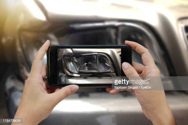 cropped hands of woman photographing damaged car - 老朽化 ストックフォトと画像