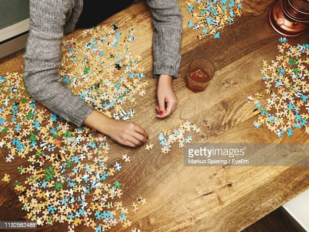 cropped hands of woman playing jigsaw puzzle on wooden table at home - raadsel stockfoto's en -beelden