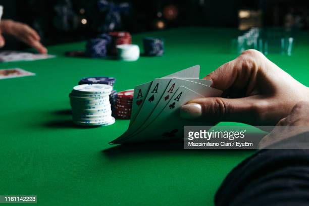 cropped hands of woman playing poker and gambling chips at casino - casino stock pictures, royalty-free photos & images