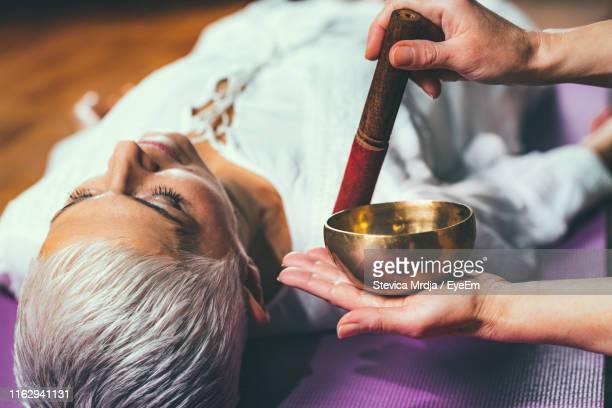 cropped hands of woman playing singing bowl for customer in spa - rin gong stock pictures, royalty-free photos & images