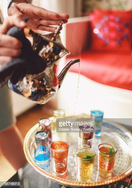 cropped hands of woman pouring tea from pot in glasses - bortes stock-fotos und bilder
