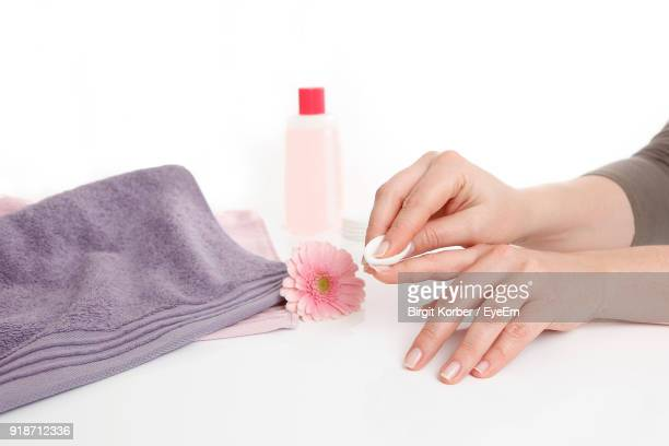 cropped hands of woman removing nail polish against white background - absence stock pictures, royalty-free photos & images