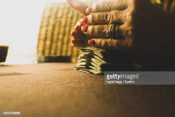 cropped hands of woman shuffling cards on table - shuffling stock photos and pictures