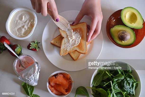 Cropped Hands Of Woman Spreading Yogurt In Bread At Table