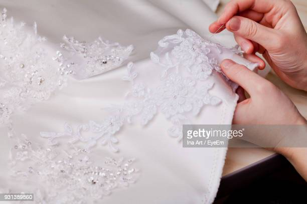 cropped hands of woman stitching wedding dress - lace textile stock pictures, royalty-free photos & images