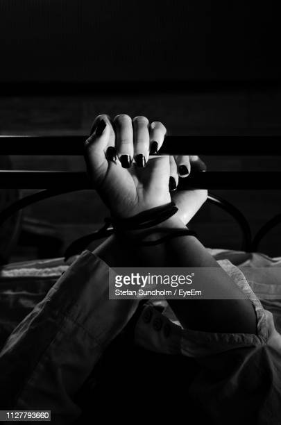 cropped hands of woman tied on bed at home - women tied to bed stock photos and pictures
