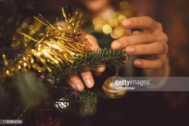 cropped hands of woman tying decoration on christmas tree - bortes stock-fotos und bilder