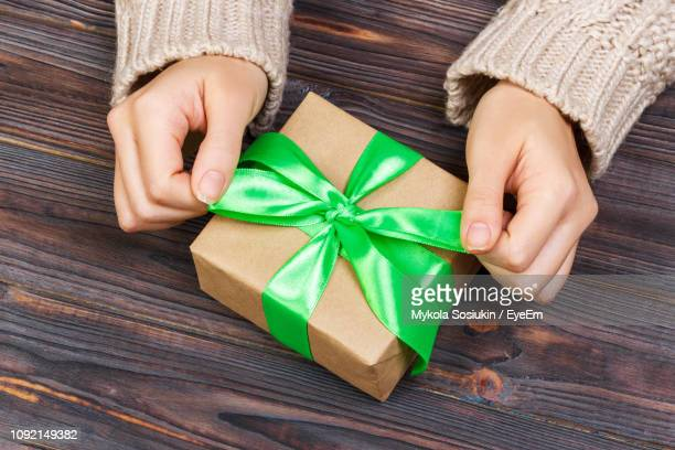 cropped hands of woman tying gift box on wooden table - 結び目 ストックフォトと画像