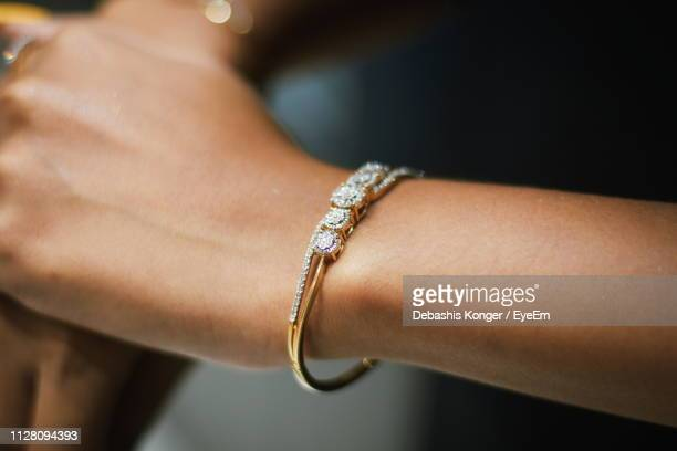 cropped hands of woman wearing bangle - bracelet stock pictures, royalty-free photos & images