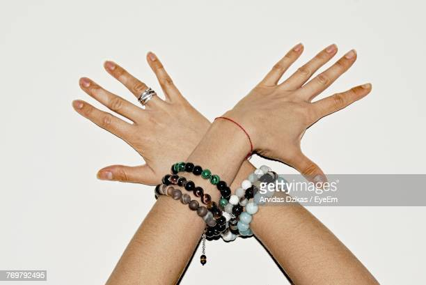 cropped hands of woman wearing bracelets over white background - armband stock-fotos und bilder