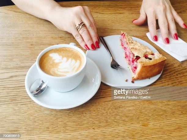 Cropped Hands Of Woman With Cake And Coffee At Wooden Table