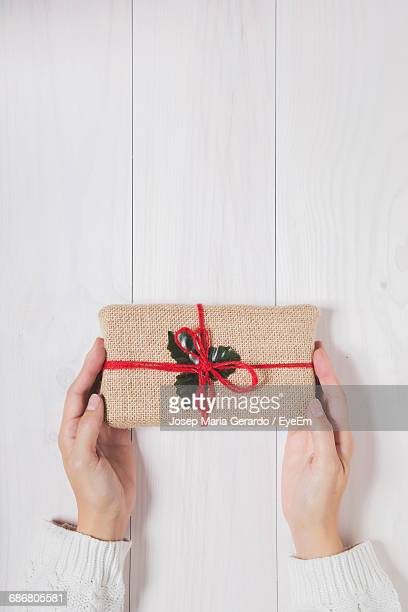 Cropped Hands Of Woman With Christmas Present On Table