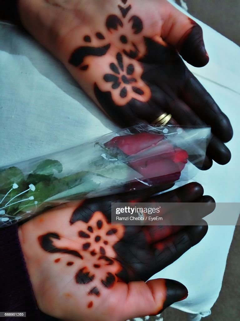 Cropped Hands Of Woman With Henna Tattoo And Red Rose Stock Photo