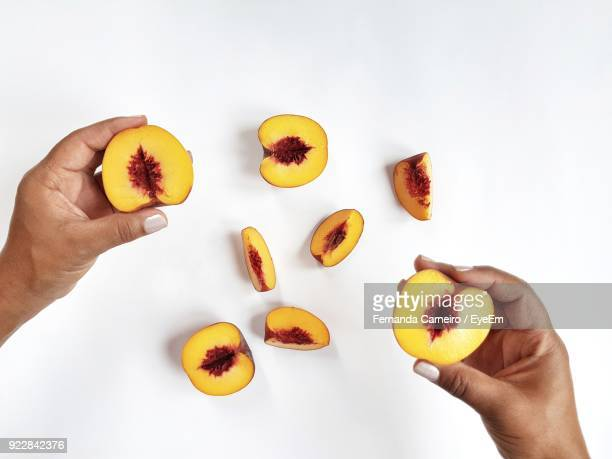 cropped hands of woman with peaches over white background - perzik stockfoto's en -beelden