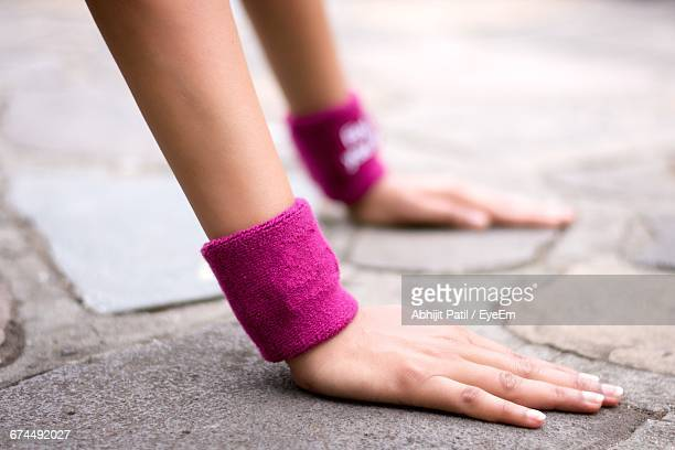 cropped hands of woman with wristbands exercising on footpath - muñequera fotografías e imágenes de stock