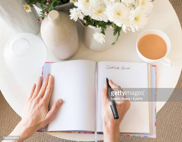 Cropped Hands Of Woman Writing In Diary By Coffee On Table At Home