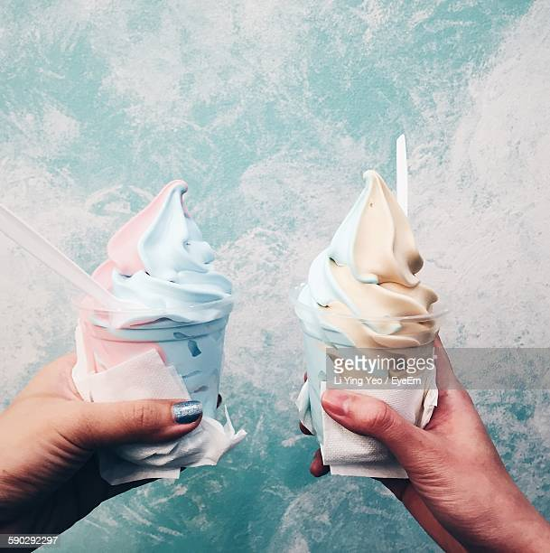 Cropped Hands Of Women Holding Ice Creams Against Wall