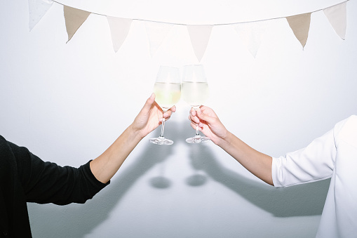 Cropped Hands Of Women Holding Wineglasses Against Wall - gettyimageskorea
