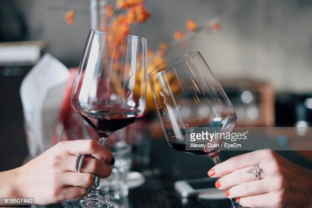 cropped hands of women toasting red wine at restaurant - brindisi bicchieri foto e immagini stock