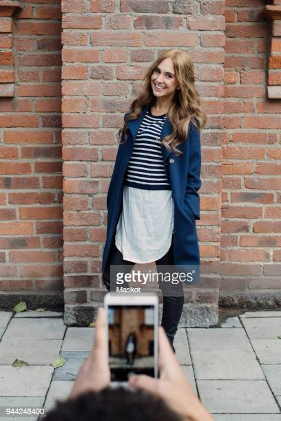 cropped hands of young man photographing fashionable woman standing against brick wall - influencer photos stock photos and pictures