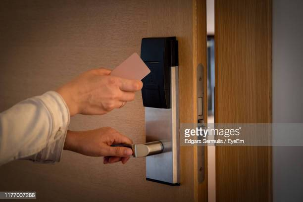 cropped hands opening door with hotel key - hotel key stock photos and pictures