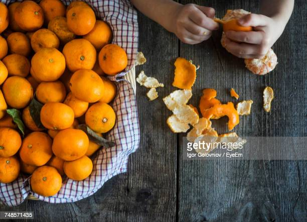 Cropped Hands Peeling Oranges On Wooden Table