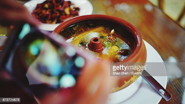 cropped hands photographing chicken soup on table - chicken soup stock photos and pictures