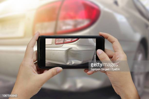 cropped hands photographing damaged car with smart phone - damaged stock photos and pictures