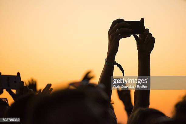 Cropped Hands Photographing Through Smart Phones During Music Festival